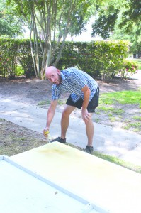 Macky James bends down to spray paint a board at the Board Paint Day last Friday