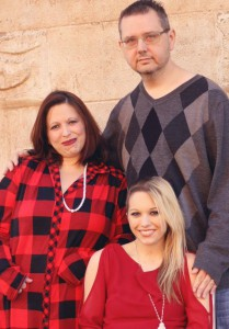 Carissa Sawyer and her parents smile during a holiday photo session.