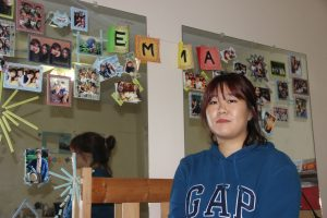 Eunhui Kim hangs pictures in her room of old and new friends.